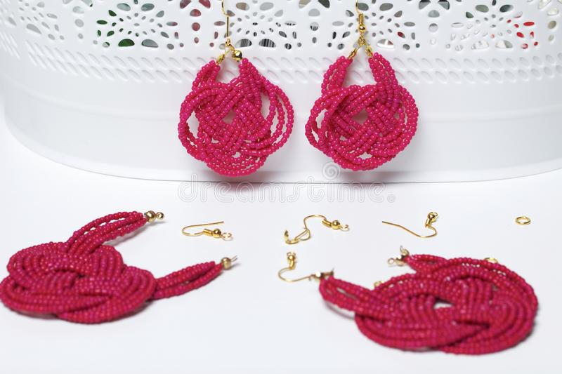 Earrings from beads handmade. Pink colour. Hang on the stand. Nearby are scattered ear wires and other accessories. Needlework at. Home. Bead jewelery royalty free stock photography