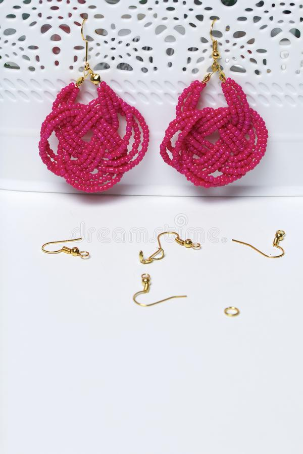Earrings from beads handmade. Pink colour. Hang on the stand. Nearby are scattered ear wires and other accessories. Needlework at. Home. Bead jewelery royalty free stock photos