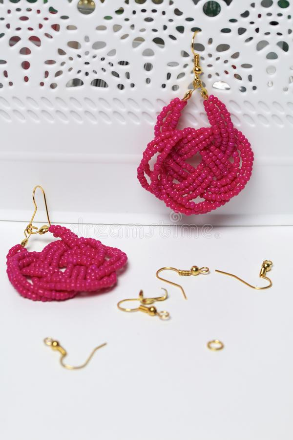 Earrings from beads handmade. Pink colour. Hang on the stand. Nearby are scattered ear wires and other accessories. Needlework at. Home. Bead jewelery stock photos