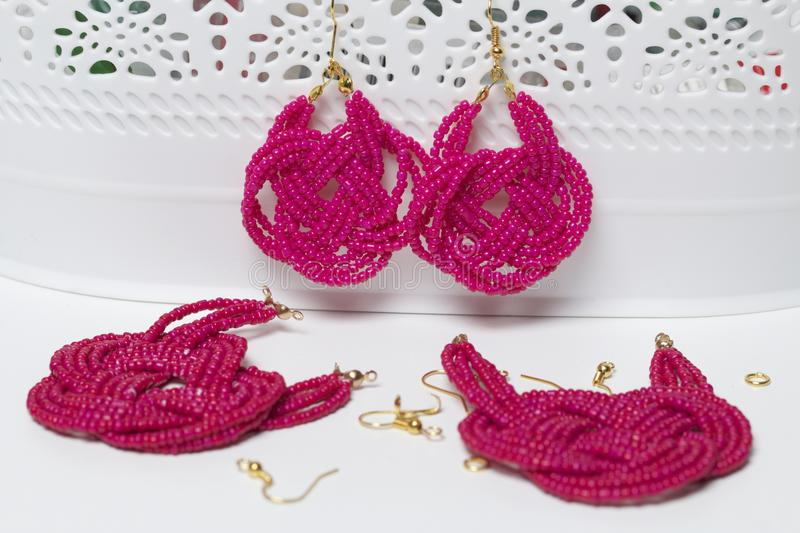 Earrings from beads handmade. Pink colour. Hang on the stand. Nearby are scattered ear wires and other accessories. Needlework at. Home. Bead jewelery royalty free stock photo