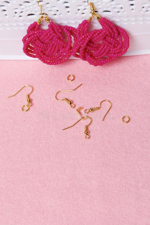 Earrings from beads handmade. Pink colour. Hang on the stand. Nearby are scattered ear wires and other accessories. Needlework at. Home. Bead jewelery stock photography