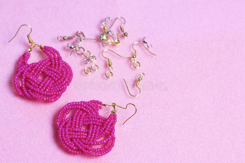 Earrings from beads handmade. Pink colour. Nearby are scattered ear wires and other accessories. Needlework at home. Bead jewelery.  royalty free stock images