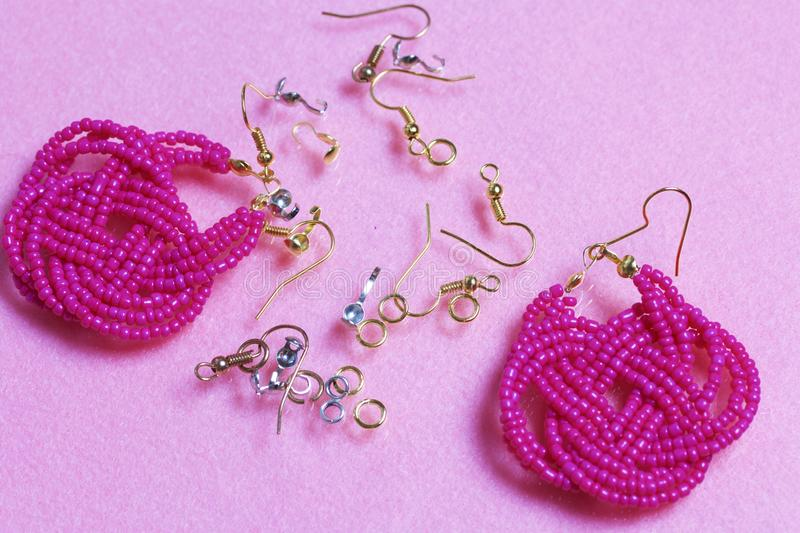 Earrings from beads handmade. Pink colour. Nearby are scattered ear wires and other accessories. Needlework at home. Bead jewelery.  stock photography