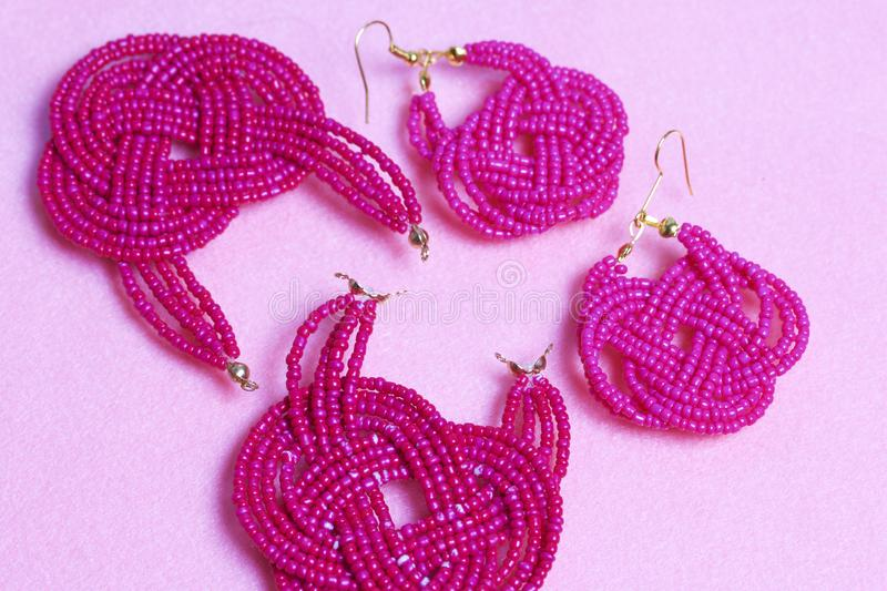 Earrings from beads handmade. Pink colour. Nearby are scattered ear wires and other accessories. Needlework at home. Bead jewelery.  stock image