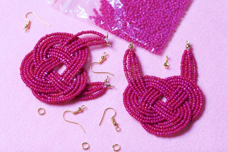 Earrings from beads handmade. Pink colour. Nearby are scattered ear wires and other accessories. Needlework at home. Bead jewelery.  royalty free stock photos