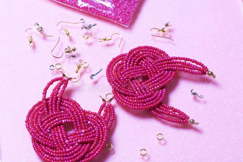 Earrings from beads handmade. Pink colour. Nearby are scattered ear wires and other accessories. Needlework at home. Bead jewelery.  royalty free stock photography