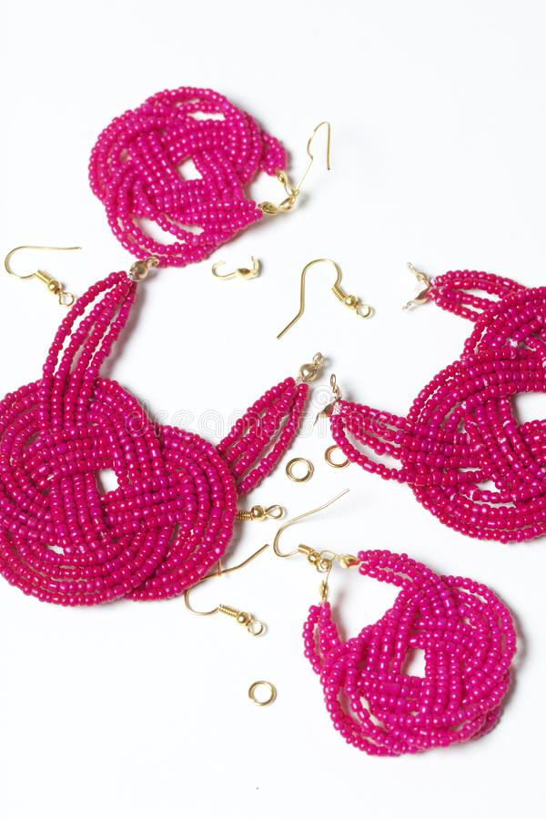 Earrings from beads handmade. Pink colour. Nearby are scattered ear wires and other accessories. Needlework at home. Bead jewelery.  stock photos