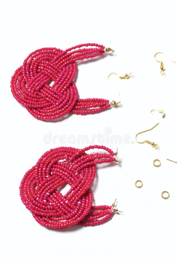 Earrings from beads handmade. Pink colour. Nearby are scattered ear wires and other accessories. Needlework at home. Bead jewelery.  stock images