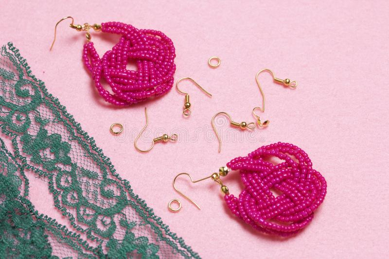 Earrings from beads handmade. Pink colour. Nearby are scattered ear wires and other accessories. Needlework at home. Bead jewelery.  royalty free stock photo