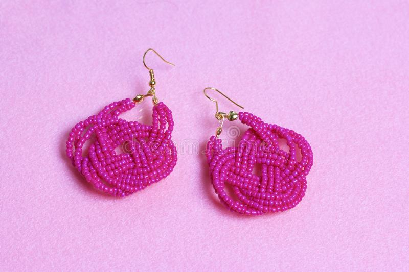 Earrings from beads handmade. Pink colour. Needlework at home. Bead jewelery. Earrings from beads handmade. Pink colour. Needlework at home. Bead jewelery royalty free stock image