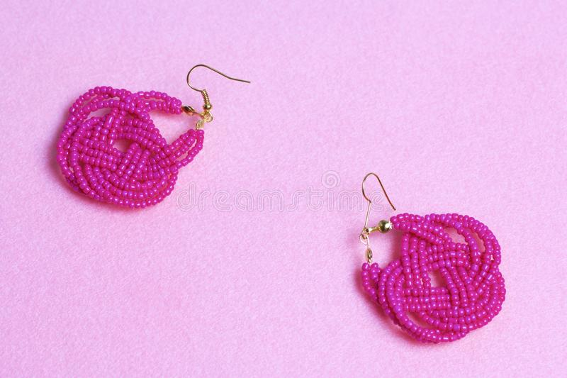 Earrings from beads handmade. Pink colour. Needlework at home. Bead jewelery. Earrings from beads handmade. Pink colour. Needlework at home. Bead jewelery stock photos