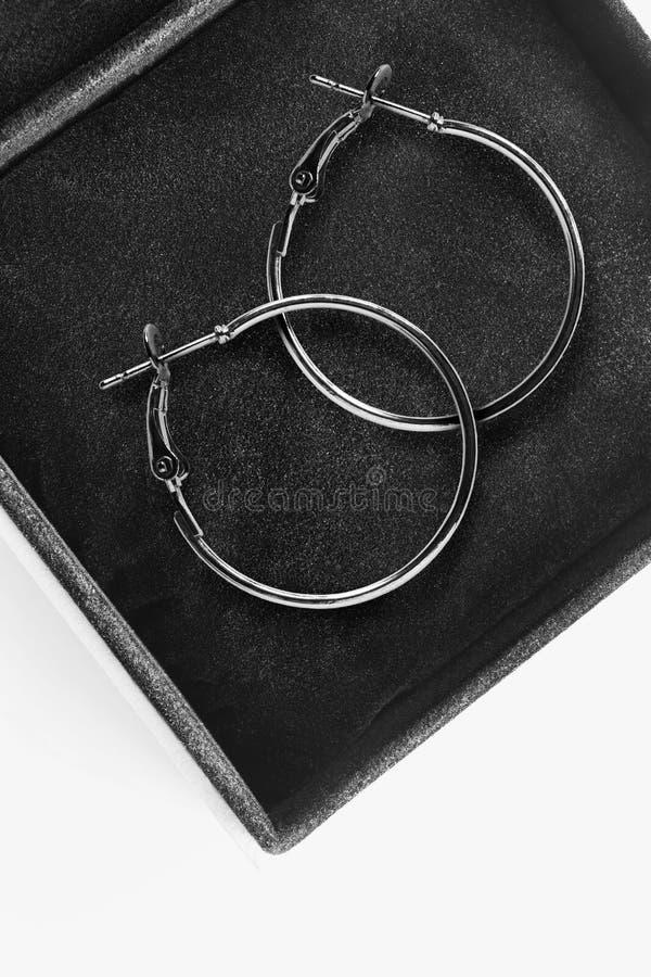Earrings in a box. Pair of elegant silver hoops earrings in black jewel box closeup stock photography