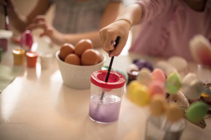 Ears are here, children are preparing. Little girls coloring Easter egg royalty free stock photography