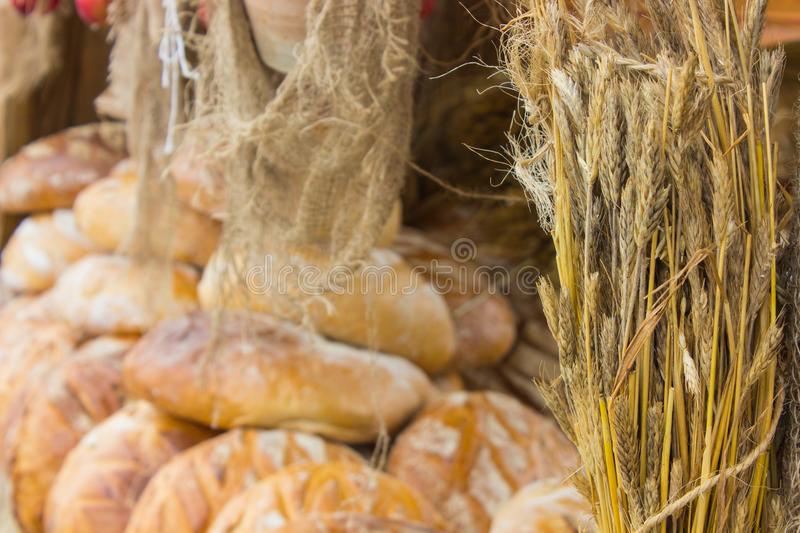 Ears of rye grain and freshly baked traditional loaves of rye bread on stall stock photography