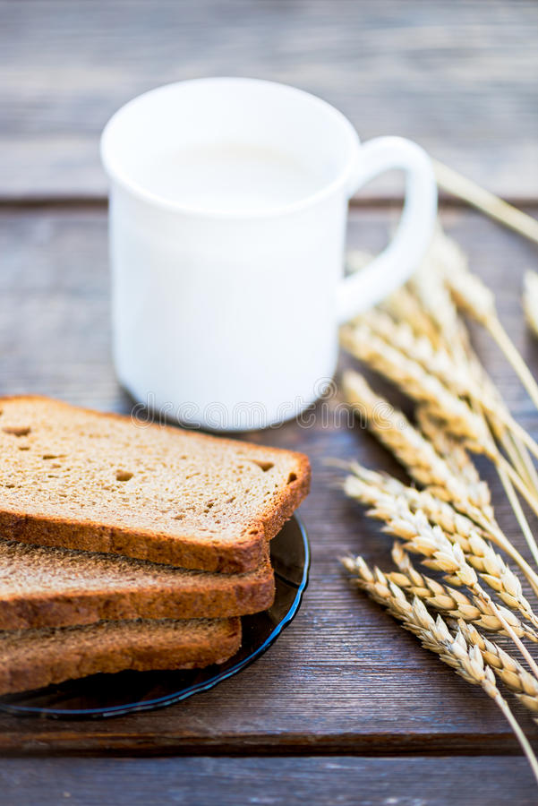 Ears of Wheat, Bread and Milk on Wooden Background royalty free stock images
