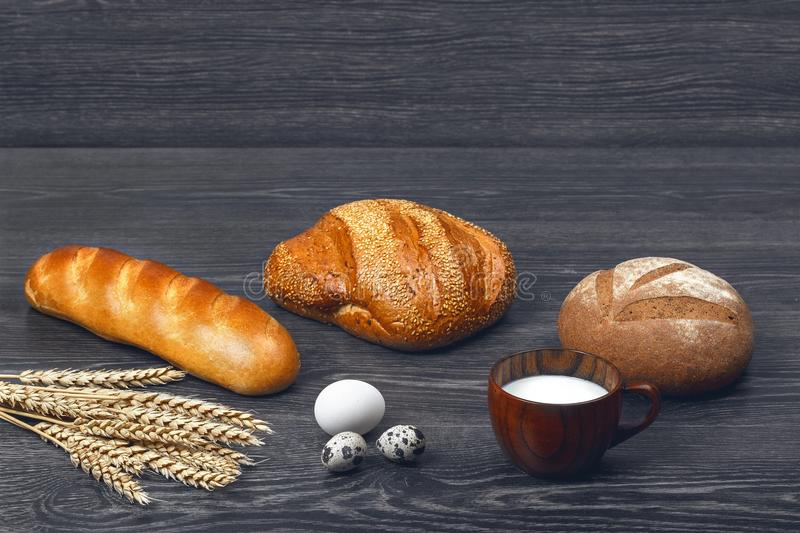Ears of wheat, chicken and quail eggs, glass of milk, freshly baked bread and a loaf on wooden background. royalty free stock image