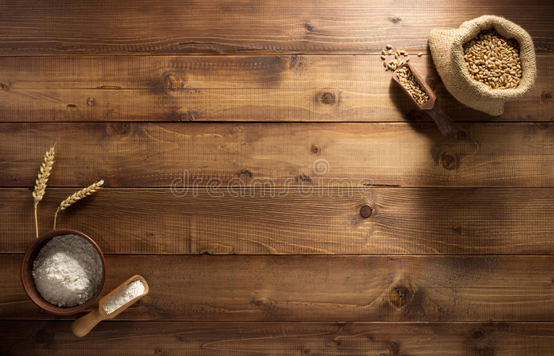 Ears and wheat flour on wood royalty free stock images