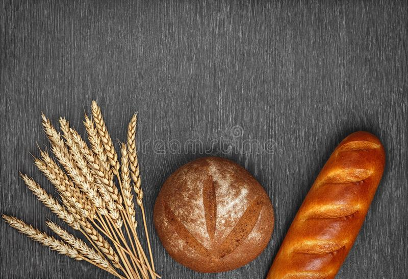 Ears of wheat, freshly baked bread and a loaf on wooden background. royalty free stock photo
