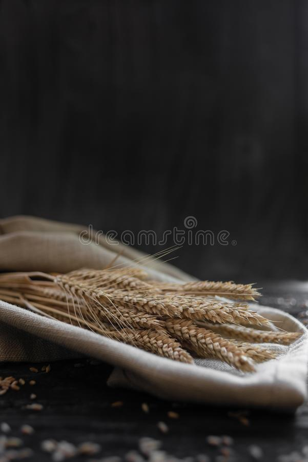 Ears of wheat lie on a wooden table. There is a place under the text stock photos