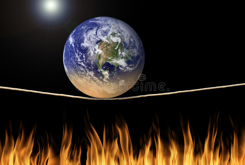 Earth balancing on tightrope over fire environmental climate change message stock photos