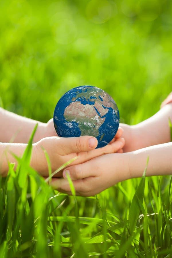 Earth in children`s hands stock images