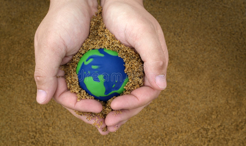 Earth Day concept. Care for planet: Environmentally Friendly Earth Day Conceptual image of Hands holding sand with small green and blue globe royalty free stock images