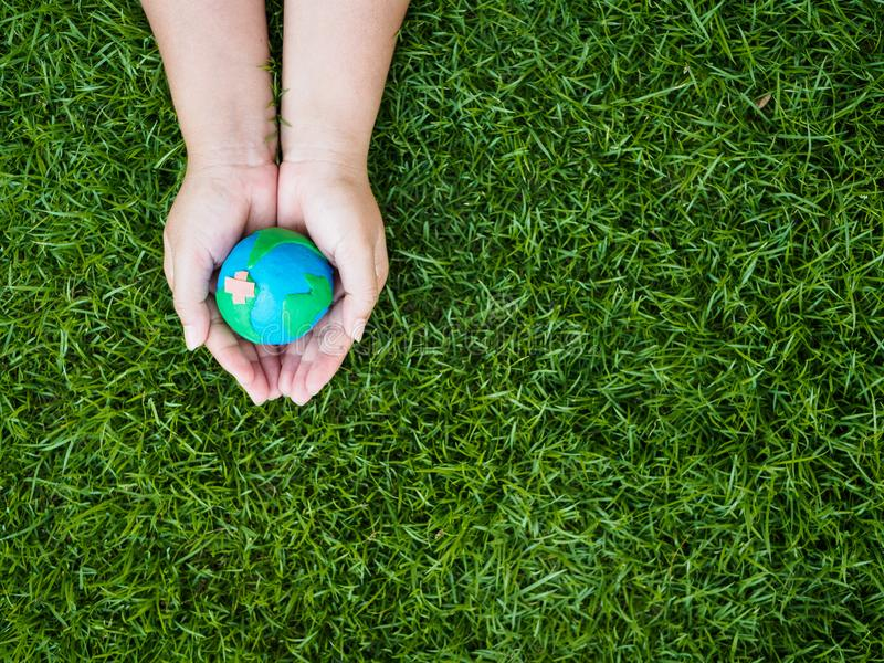 earth day. earth in hands and green grass field background. environment save earth concept. stock photos
