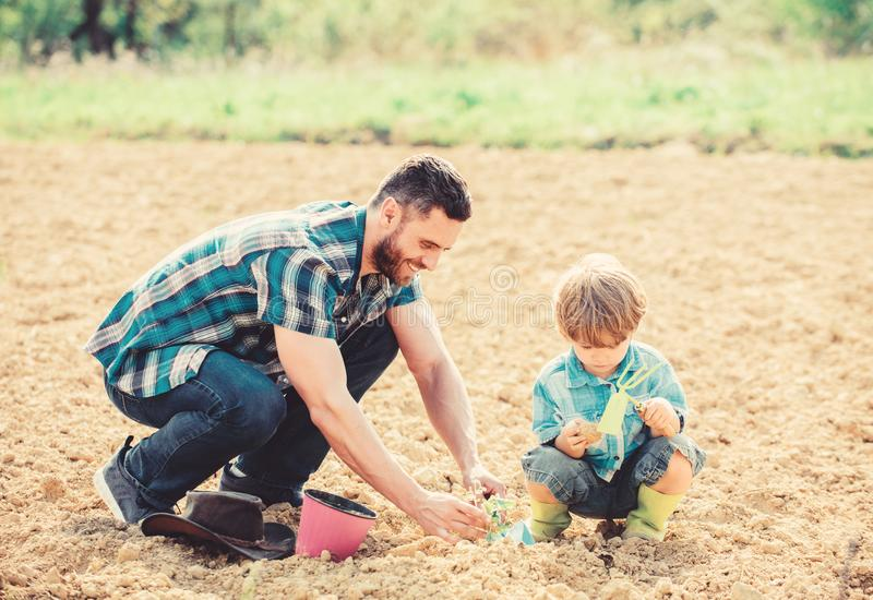 Earth day. small boy child help father in farming. happy earth day. Family tree. rich natural soil. Eco farm. Enjoying royalty free stock image