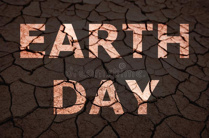 Earth Day text on dry soil stock photo