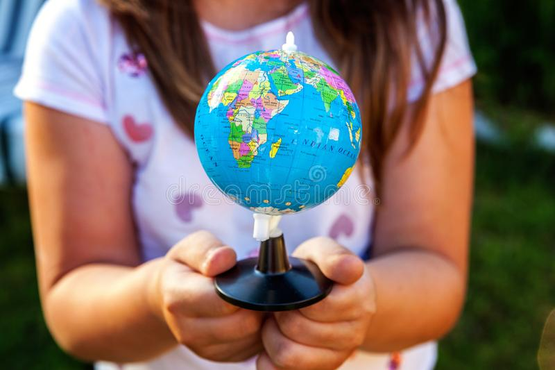Earth globe in children hands. Little girl holding symbol world map. Environment conservation, save planet, unity, peace and protect concept stock photos