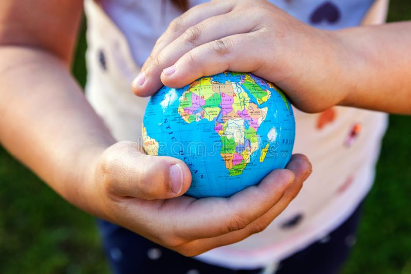 Earth globe in children hands. Little girl holding symbol world map. Environment conservation, save planet, unity, peace and protect concept stock photo