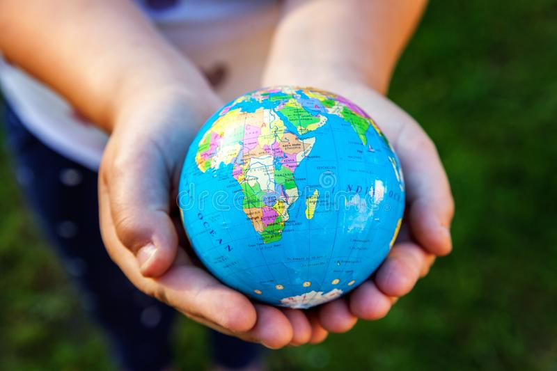Earth globe in children hands. Little girl holding symbol world map. Environment conservation, save planet, unity, peace and protect concept stock photography