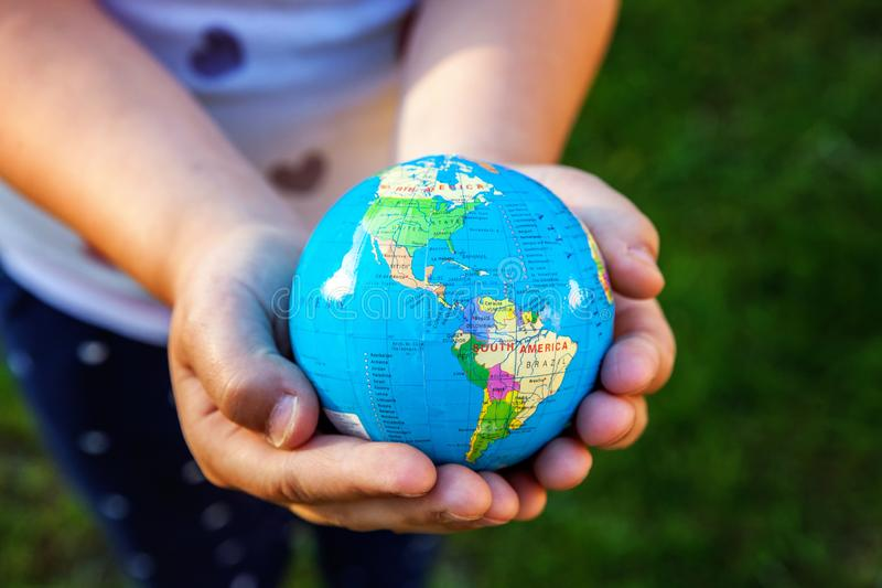 Earth globe in children hands. Little girl holding symbol world map. Environment conservation, save planet, unity, peace and protect concept royalty free stock images