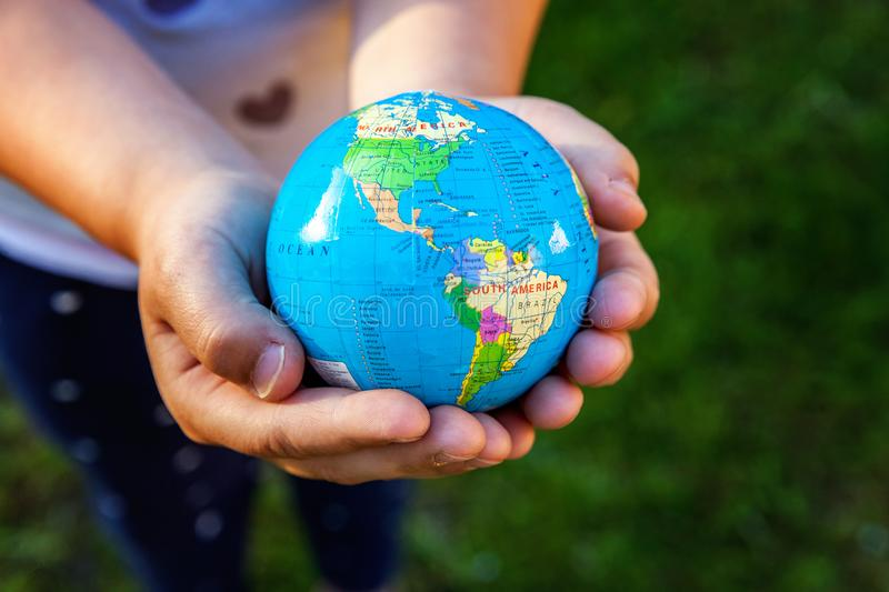 Earth globe in children hands. Little girl holding symbol world map. Environment conservation, save planet, unity, peace and protect concept stock images