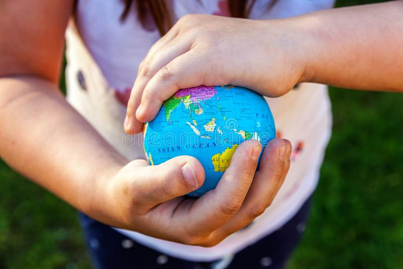 Earth globe in children hands. Little girl holding symbol world map. Environment conservation, save planet, unity, peace and protect concept royalty free stock photography