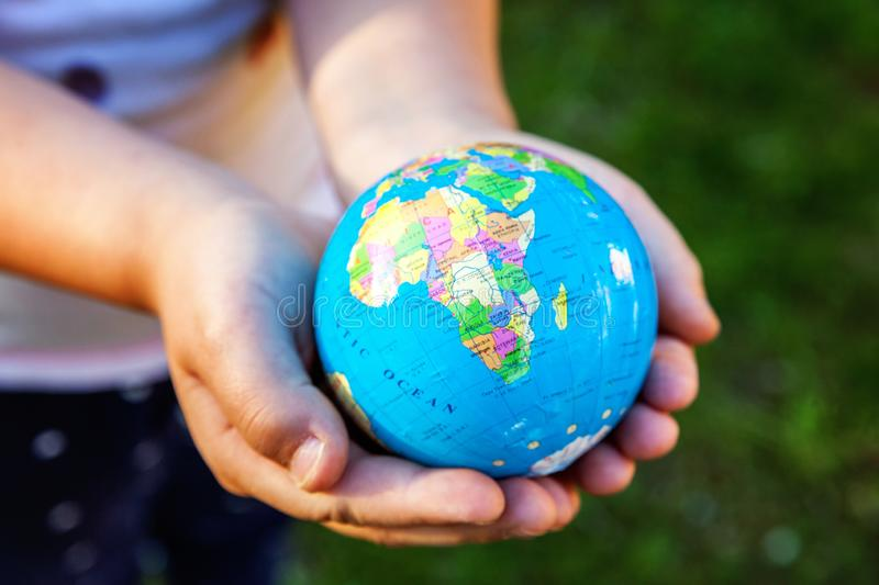 Earth globe in children hands. Little girl holding symbol world map. Environment conservation, save planet, unity, peace and protect concept royalty free stock photo