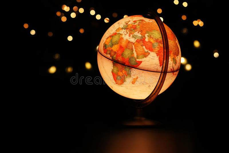 Earth globe glowing in dark starry sky. Earth over Africa and Europe in glowing desk globe in black starry sky stock photo