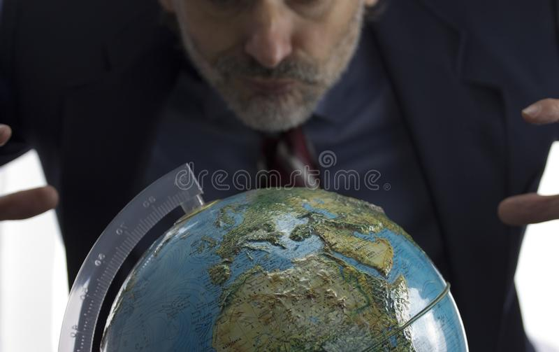 Earth globe and greedy man stock photography
