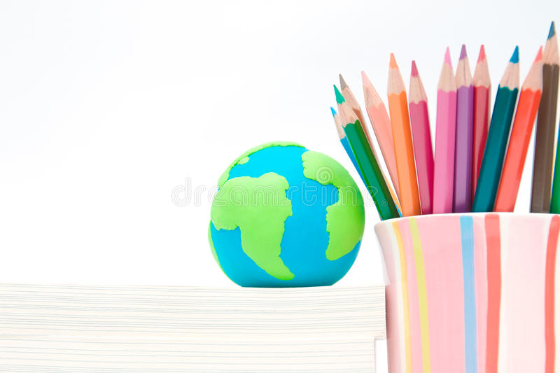 Earth globe made of clay on books stack stock photo