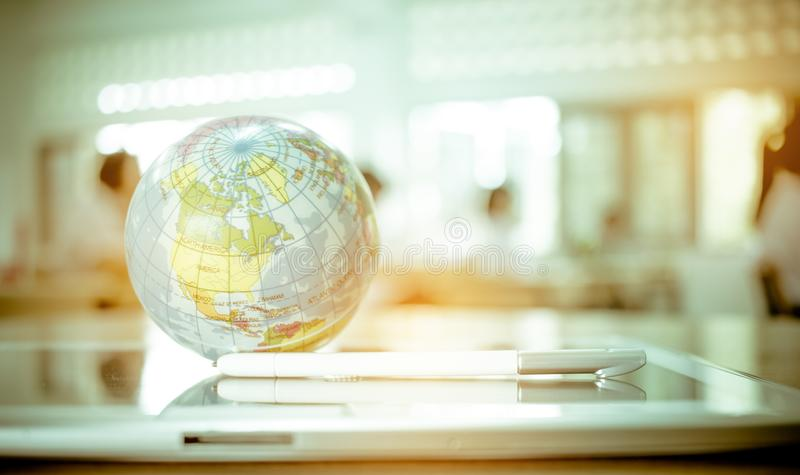 Earth globe model ball map with class room background on tablet. In classroom. Concept for global international educaiton or communications, politics royalty free stock photo