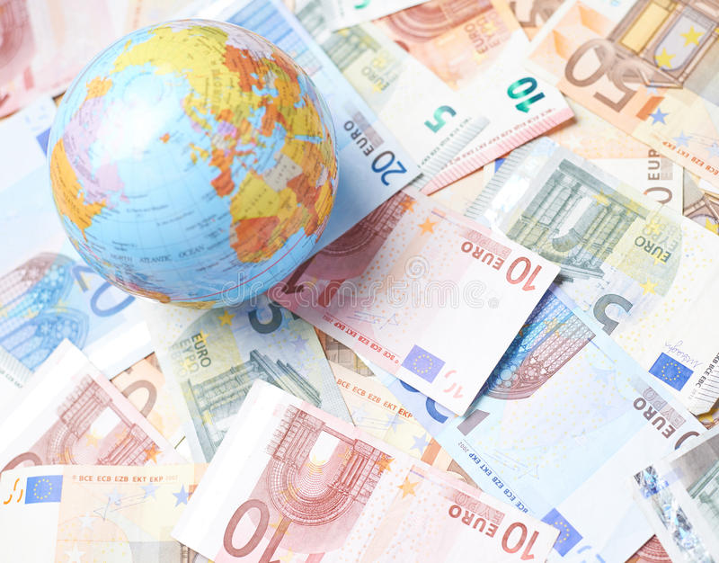 Earth globe over the pile of money. Tiny Earth globe over the surface covered with the multiple bank note bills royalty free stock images