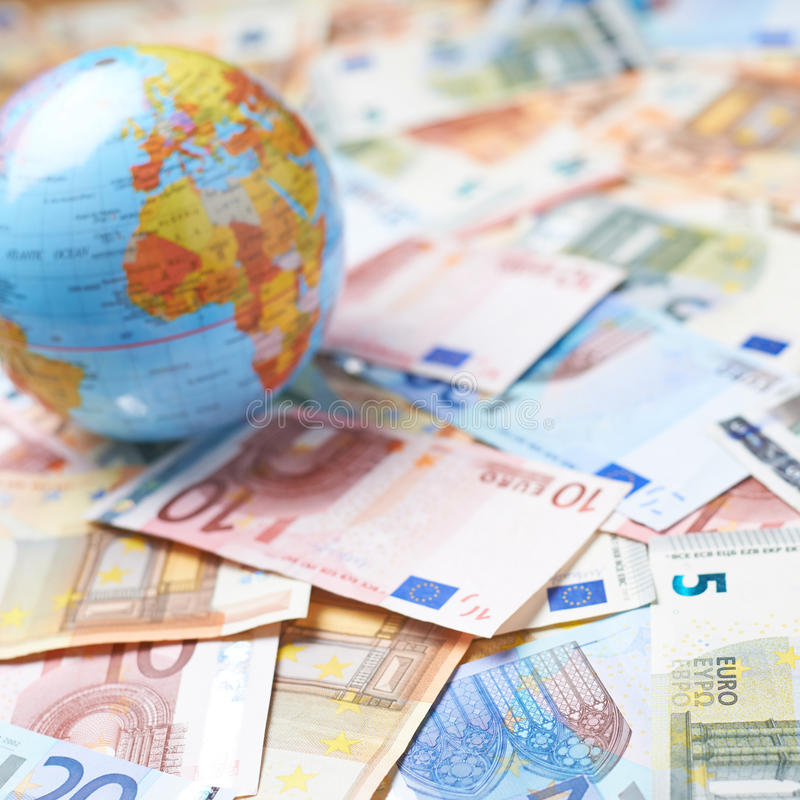 Earth globe over the pile of money. Tiny Earth globe over the surface covered with the multiple bank note bills, shallow depth of field composition royalty free stock photos