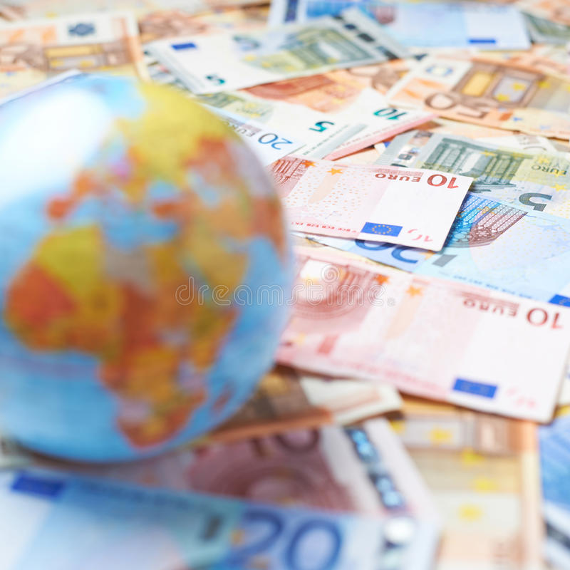 Earth globe over the pile of money. Tiny Earth globe over the surface covered with the multiple bank note bills, shallow depth of field composition royalty free stock photo