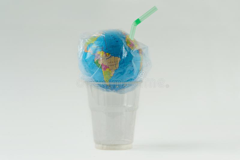 Earth globe in a plastic bag with straw over plastic glass - Concept of ecology and stop plastic pollution stock photo