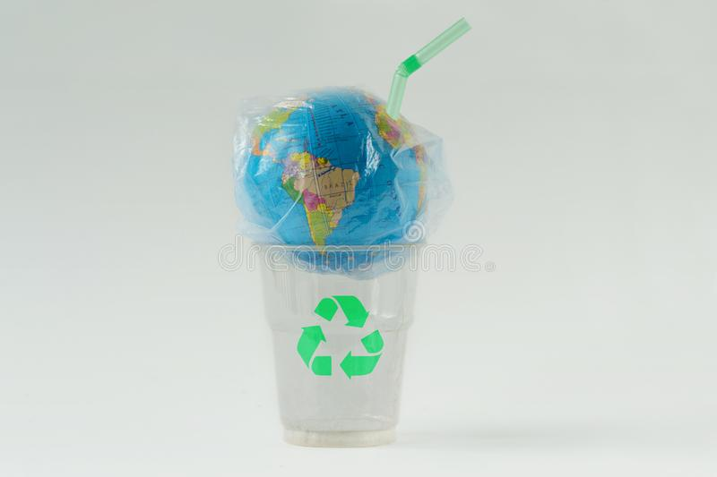Earth globe in a plastic bag with straw on plastic glass with recycling symbol - Concept of ecology and stop plastic pollution royalty free stock images
