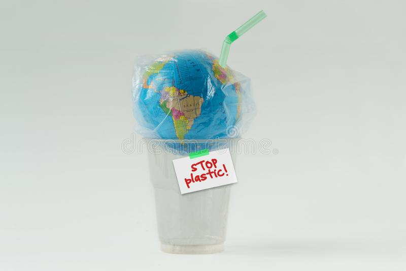 Earth globe in a plastic bag with straw on plastic glass and the written Stop plastic! - Concept of ecology and stop plastic stock photo