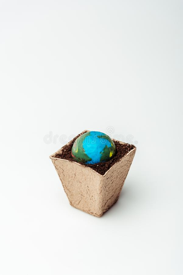Earth model in flower pot with soil. Isolated on white, earth day concept royalty free stock photography