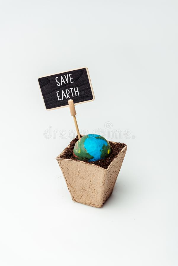 Earth model and sign save earth in flower pot. Isolated on white, earth day concept stock photo