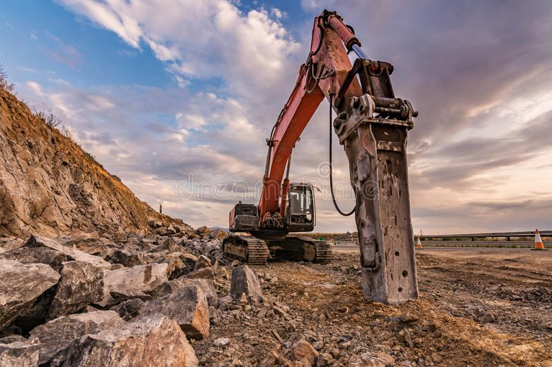 Earth moving by a bulldozer in the construction of a road in Spain. Hydraulic hammer for backhoe stock photos