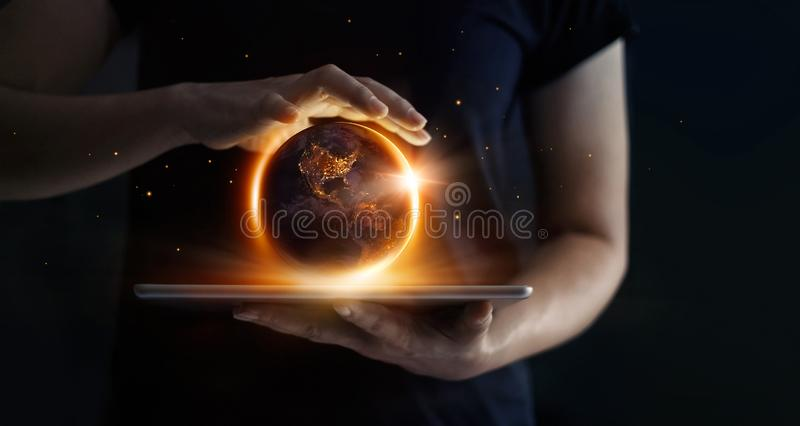 Earth at night was holding in human hands and technology. royalty free stock photography